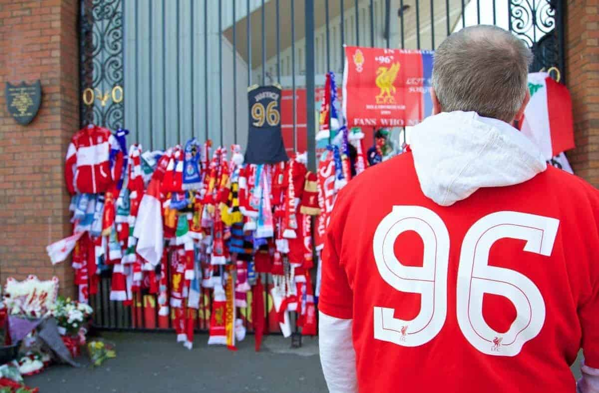LIVERPOOL, ENGLAND - Tuesday, April 15, 2014: A supporter takes a moment to look at the tributes tied to the Shankly Gates before the 25th Anniversary Hillsborough Service at Anfield. (Pic by David Rawcliffe/Propaganda)