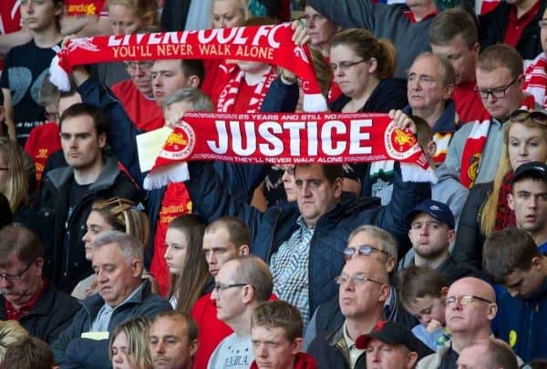 LIVERPOOL, ENGLAND - Tuesday, April 15, 2014: A Liverpool supporter holds up a scarf 'Justice' during the 25th Anniversary Hillsborough Service at Anfield. (Pic by David Rawcliffe/Propaganda)