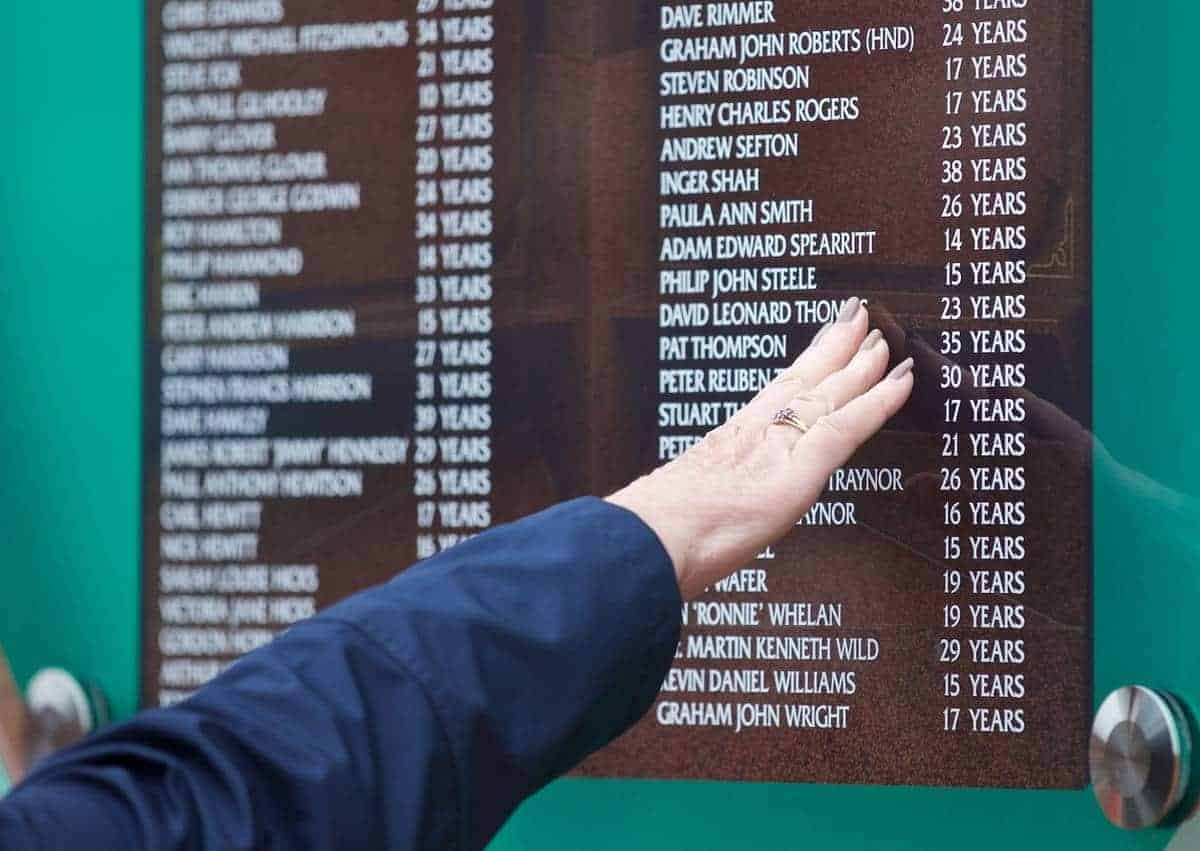 LIVERPOOL, ENGLAND - Wednesday, April 15, 2015: A supporter touches the temporary Memorial before the 26th Anniversary Hillsborough Service at Anfield. (Pic by David Rawcliffe/Propaganda)