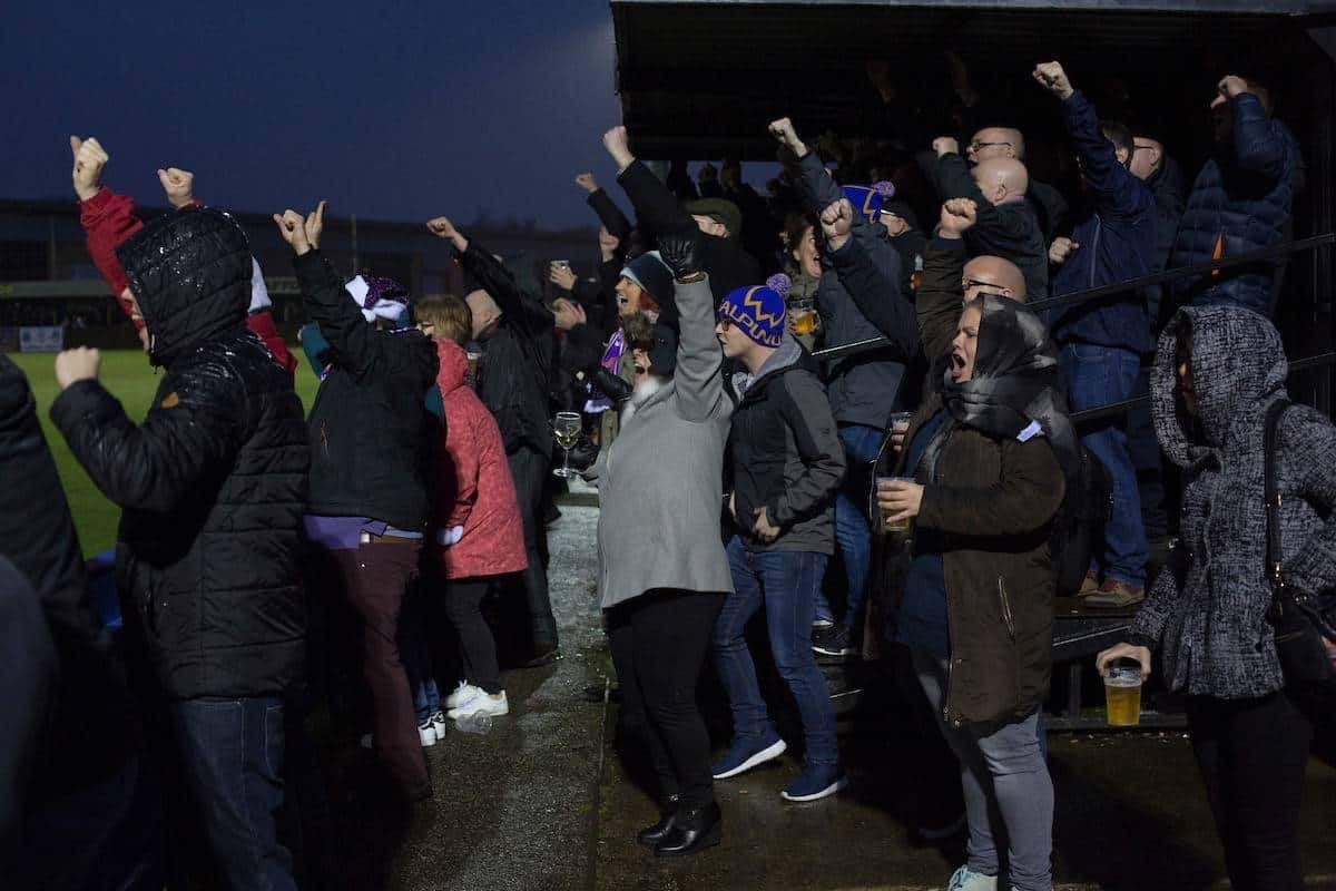 Home supporters celebrating their team's fourth goal at the Delta Taxis Stadium, Bootle, Merseyside as City of Liverpool hosted Holker Old Boys in a North West Counties League division one match. Founded in 2015, and aiming to be the premier non-League club in Liverpool, City were admitted to the League at the start of the 2016-17 season and were using Bootle FC's ground for home matches. A 6-1 victory over their visitors took 'the Purps' to the top of the division, in a match watched by 483 spectators.