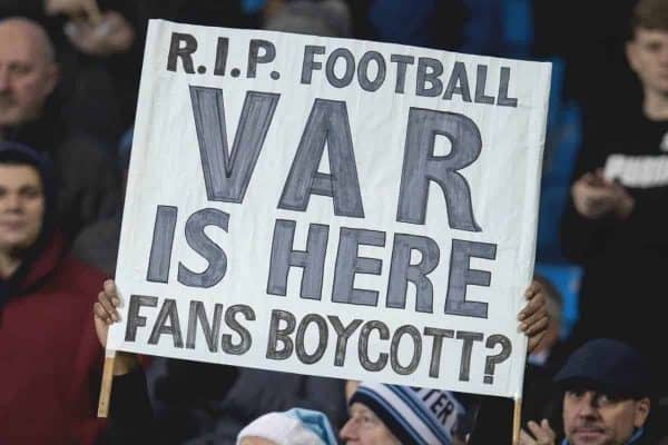 """MANCHESTER, ENGLAND - Wednesday, January 1, 2020: A supporter holds up a sign """"RIP football VAR is here. Fans Boycott?"""" as two stewards stand over him during the FA Premier League match between Manchester City FC and Everton FC at the City of Manchester Stadium. (Pic by David Rawcliffe/Propaganda)"""