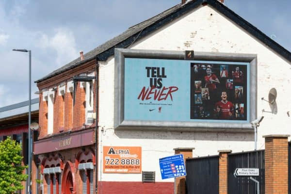 "LIVERPOOL, ENGLAND - Monday, August 3, 2020: A Nike advert ""Tell Us Never"" is shown on a hording on The Albert pub oustide Liverpool's Spion Kop at Anfield. Liverpool's new kit supplier Nike replaces New Balance in a five year deal reported to be worth $39.5 per year. (Pic by David Rawcliffe/Propaganda)"