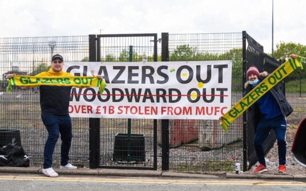 """MANCHESTER, ENGLAND - Sunday, May 2, 2021: Two Manchester United supporters protest against the owners with """"Glazers Out"""" scarves and banner outside the ground before the FA Premier League match between Liverpool FC and Manchester United FC at Old Trafford which was postponed due to safety concerns after a number of supporters entered the stadium. (Pic by David Rawcliffe/Propaganda)"""