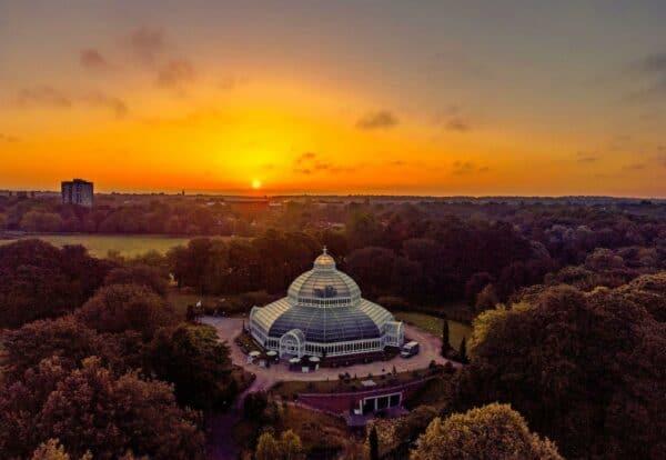 The sun rises behind the Sefton Park Palm House