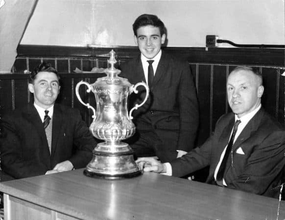 LIVERPOOL, ENGLAND - 1965: Liverpool FC manager Bill Shankly with the FA Cup trophy and two local journalists.