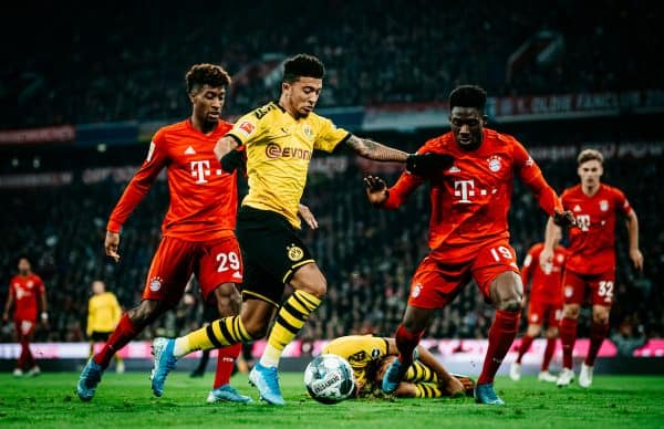 MUNICH, GERMANY - NOVEMBER 09: Jadon Sancho of Dortmund in action against Kingsley Coman of Bayern Muenchen (L) and Alphonso Davies of Bayern Muenchen during the Bundesliga match between FC Bayern M¸nchen and Borussia Dortmund at Allianz Arena on November 09, 2019 in Munich, Germany. (Photo by Alexander Scheuber/Bundesliga/Bundesliga Collection via Getty Images)