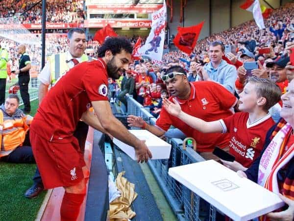 Liverpool's Mohamed Salah receives a gift from supporters as the players perform a lap of honour after the FA Premier League match between Liverpool FC and Brighton & Hove Albion FC at Anfield. Liverpool won 4-0. (Pic by David Rawcliffe/Propaganda)