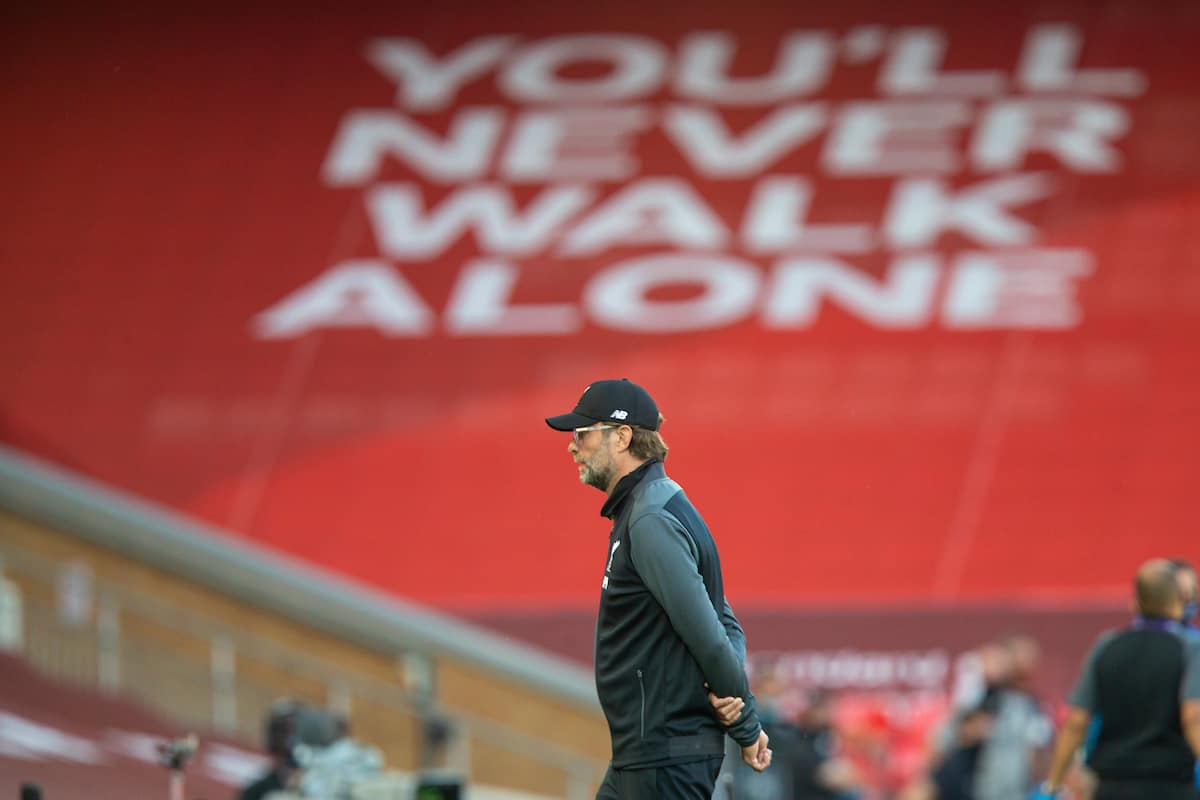 "LIVERPOOL, ENGLAND - Wednesday, June 24, 2020: Liverpool's manager Jürgen Klopp in front of a banner ""You'll Never Walk Alone"" before the FA Premier League match between Liverpool FC and Crystal Palace FC at Anfield. The game was played behind closed doors due to the UK government's social distancing laws during the Coronavirus COVID-19 Pandemic. (Pic by David Rawcliffe/Propaganda)"