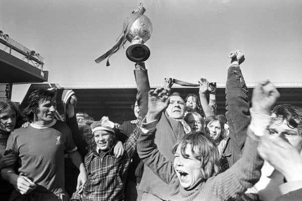 Liverpool manager Bill Shankly holds aloft the League Championship trophy at Anfield today, and the joy on the face of the young supporter says it all. Liverpool just clinched the title by drawing 0-0 with Leicester. 1973 (PA Images)