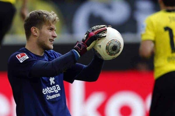 Mainz goalkeeper Loris Karius, center, holds the ball while Dortmund's Marco Reus, left, celebrates after scoring during the German first division Bundesliga soccer match between BvB Borussia Dortmund and Mainz 05 in Dortmund, Germany, Saturday, April 19, 2014. (AP Photo/Frank Augstein)