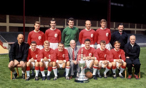 League champions Liverpool pose with the trophy: (back row, l-r) Gordon Milne, Gerry Byrne, Tommy Lawrence, Ronnie Moran, Wilf Stevenson, trainer Bob Paisley; (front row, l-r) trainer Reuben Bennett, Ian Callaghan, Roger Hunt, Ian St John, ?, Ron Yeats, Alf Arrowsmith, Peter Thompson, manager Bill Shankly. 12 August 1964. ( PA Photos/PA Archive/PA Images)