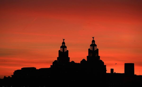 A view of the Royal Liver Building as the sun rises over Liverpool.