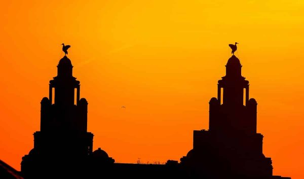 The sun sets behind the Royal Liverbuilding in Liverpool.
