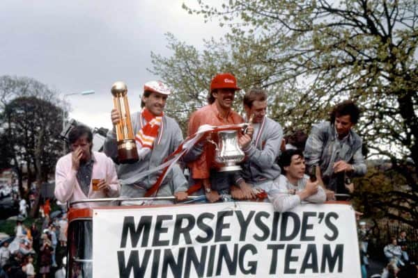 1986: Liverpool player-manager Kenny Dalglish (second l) shows off the League Championship trophy as teammate Mark Lawrenson (third l) displays the FA Cup during the team's celebratory open-topped bus journey through the city, the day after they completed the Double. The other players are Ronnie Whelan (l), Alan Hansen (second r) and Craig Johnston (r) ( PA Photos/PA Archive/PA Images)