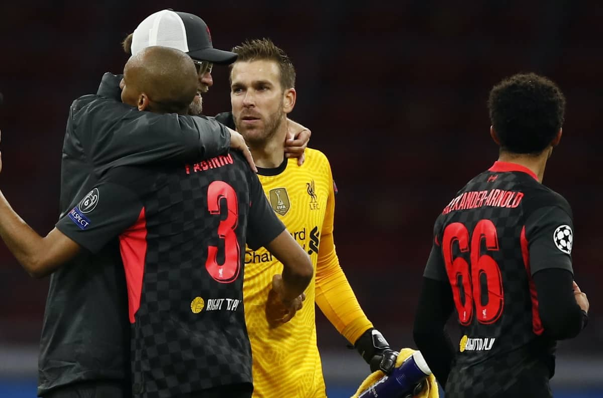 Liverpool's manager Jurgen Klopp, left, embraces his players Fabinho, left and goalkeeper Adrian, center as they celebrate their victory following the group D Champions League soccer match between Ajax and Liverpool at the Johan Cruyff ArenA in Amsterdam, Netherlands, Wednesday, Oct. 21, 2020. Liverpool won the match 1-0. (AP Photo/Peter Dejong)
