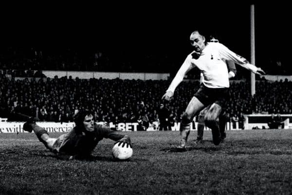 Ray Clemence dives at the feet of Tottenham's Alan Gilzean (PA)