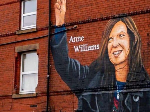 2GE9PH9 Artist Paul Curtis paints a mural of Anne Williams, the mother of Hillsborough victim Kevin Williams, on a building in the Anfield area of Liverpool. Picture date: Wednesday August 18, 2021.